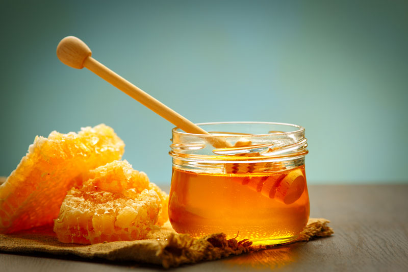 Honey pot and raw honey on a table